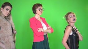 Tres mujeres jovenes hermosas en la ropa elegante que presenta en la cámara en fondo de pantalla verde almacen de video