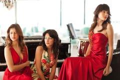 Tres mujeres jovenes hermosas en un piano Imágenes de archivo libres de regalías