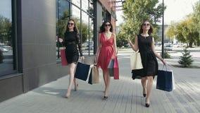 Tres mujeres jovenes preciosas que caminan abajo de la calle y que disfrutan de su día de las compras metrajes