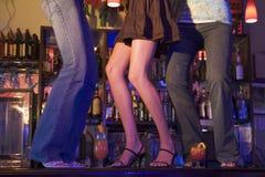 Tres mujeres jovenes que bailan en un contador de la barra Imagenes de archivo