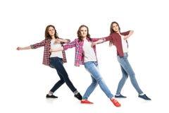 Tres mujeres jovenes que bailan sobre el fondo blanco imagen de archivo