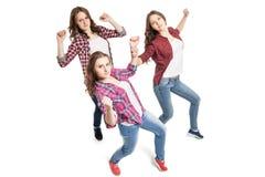 Tres mujeres jovenes que bailan sobre el fondo blanco imágenes de archivo libres de regalías