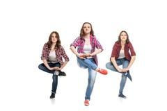 Tres mujeres jovenes que bailan sobre el fondo blanco foto de archivo