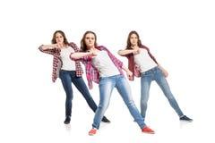 Tres mujeres jovenes que bailan sobre el fondo blanco imagenes de archivo