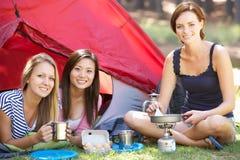 Tres mujeres jovenes que cocinan en estufa que acampa fuera de la tienda Fotos de archivo libres de regalías