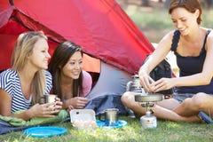 Tres mujeres jovenes que cocinan en estufa que acampa fuera de la tienda Imagen de archivo libre de regalías