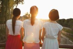 Tres mujeres jovenes que consideran rio abajo una puesta del sol imagenes de archivo