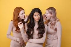 Tres mujeres jovenes que gritan en su amigo Fotos de archivo