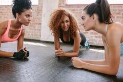 Tres mujeres jovenes que hacen flexiones de brazos imagenes de archivo