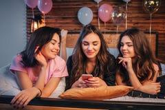 Tres mujeres jovenes que mienten en cama en sitio Muchacha en teléfono medio del control en manos Sus frieds lo miran Sonríen Jov imagen de archivo