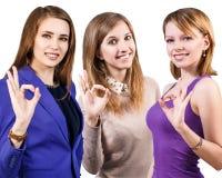 Tres mujeres jovenes que muestran la muestra ACEPTABLE Foto de archivo libre de regalías