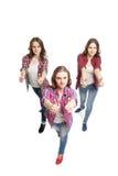 Tres mujeres jovenes que presentan sobre el fondo blanco imagen de archivo