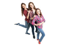 Tres mujeres jovenes que presentan sobre el fondo blanco imágenes de archivo libres de regalías