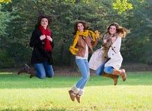 Tres mujeres jovenes que saltan alegre en el parque Imágenes de archivo libres de regalías
