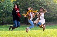 Tres mujeres jovenes que saltan alegre en el parque Imagen de archivo