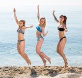 Tres mujeres jovenes que saltan en la playa arenosa Foto de archivo