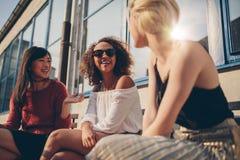 Tres mujeres jovenes que se encuentran en el café al aire libre foto de archivo