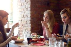 Tres mujeres jovenes que se relajan sobre almuerzo Fotografía de archivo libre de regalías