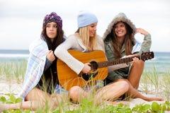 Tres mujeres jovenes que se sientan en la playa fría con el GUI Imagen de archivo