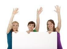 Tres mujeres jovenes que sostienen una bandera y que la saludan foto de archivo libre de regalías