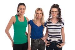 Tres mujeres jovenes sonrientes que se unen y que presentan Imagen de archivo