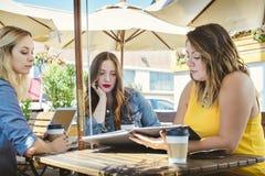 Tres mujeres jovenes tienen una reunión de negocios en una cafetería fotos de archivo libres de regalías