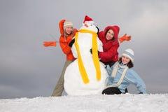 Tres mujeres jovenes y muñeco de nieve 2 Fotografía de archivo libre de regalías