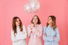 Tres mujeres lindas morenas en los pijamas rayados coloridos que presentan encendido Imagen de archivo libre de regalías