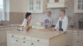 Tres mujeres maduras que comunican charlando en casa la colocación cerca de la tabla moderna en el medio de cocina Señoras mayore almacen de metraje de vídeo