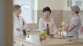Tres mujeres maduras que comunican en casa la colocación cerca de la tabla moderna en la cocina Señora que cuenta historia emotio almacen de metraje de vídeo