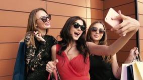 Tres mujeres preciosas que toman la foto contra fondo anaranjado Cámara lenta metrajes