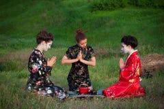 Tres mujeres que beben té de una manera asiática Fotos de archivo libres de regalías