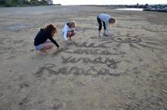 Tres mujeres que dibujan dentro de una arena en la playa Imagenes de archivo