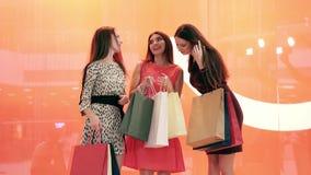 Tres mujeres que hacen compras con muchos panieres en las manos que miran sus compras metrajes