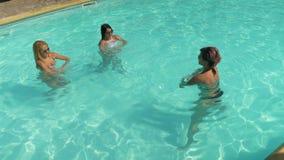 Tres mujeres que hacen la aptitud que ejercita en el agua de la piscina metrajes