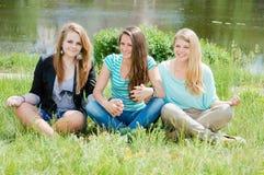 Tres mujeres que ligan hermosas de relajación se sientan en hierba verde Fotos de archivo libres de regalías