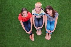 Tres mujeres que ligan hermosas de relajación se sientan en hierba verde Foto de archivo libre de regalías