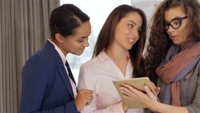 Tres mujeres que miran la tableta la oficina metrajes