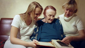 Tres mujeres que miran a través del archivo de la familia metrajes
