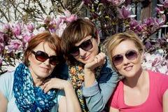 Tres mujeres que presentan con la magnolia floreciente Imágenes de archivo libres de regalías