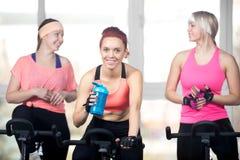 Tres mujeres que se relajan después de ejercicios cardiios en ciclos Imagen de archivo libre de regalías