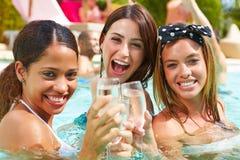 Tres mujeres que tienen partido en piscina que bebe Champán Fotografía de archivo libre de regalías