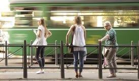 Tres mujeres rubias que se colocan en un publi de la parada y el esperar de autobús fotografía de archivo libre de regalías