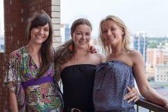 Tres mujeres sonrientes amigos que se unen y que abrazan en balcón del edificio Fotografía de archivo libre de regalías