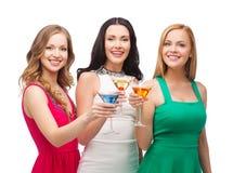 Tres mujeres sonrientes con los cócteles imagenes de archivo