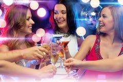 Tres mujeres sonrientes con los cócteles en club Imagenes de archivo
