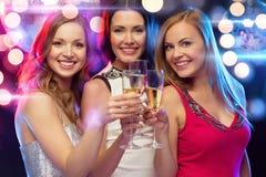 Tres mujeres sonrientes con los vidrios del champán Imágenes de archivo libres de regalías