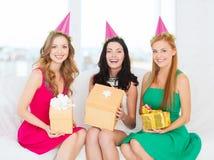 Tres mujeres sonrientes en sombreros rosados con las cajas de regalo Foto de archivo