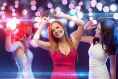 Tres mujeres sonrientes que bailan en el club Fotografía de archivo