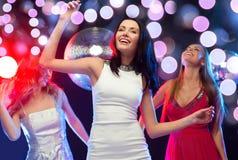 Tres mujeres sonrientes que bailan en el club Foto de archivo libre de regalías